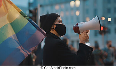 Young woman with face mask speaking into the megaphone while holding rainbow flag in crowd