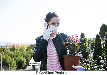 Young woman with face masks outdoors shopping in garden ...