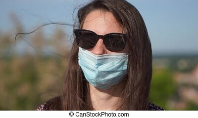 Young woman with face medical mask and sunglasses outdoors on summer day. new normal. High quality FullHD footage