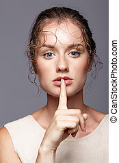 Young woman with finger over lips