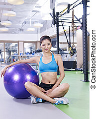 young woman with fitness ball - young woman sitting next to...