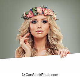 Young Woman with Flowers Hairstyle Holding White Banner for Text. Blonde Beauty