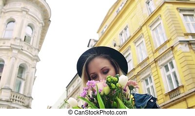 Young woman with flowers in sunny spring town. - Portrait of...