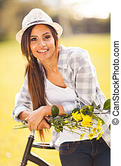 young woman with flowers posing next to a bike