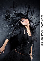 Young woman with fluttering hair. On dark wall background.
