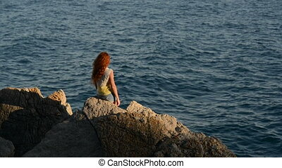 Young woman with flying hair sitting on a rocky seashore