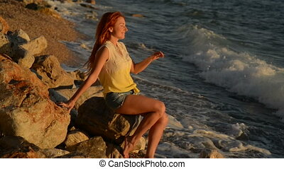 Young woman with flying hair sitting on the rocky beach of the Adriatic Sea