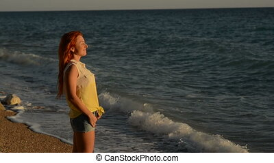 Young woman with flying hair standing on the rocky beach of the Adriatic Sea