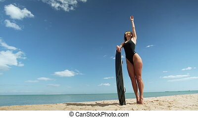 young woman with flying kiteboard on tropical beach at...