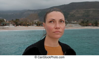 Young woman with freckles looks around the coast in cloudy weather.