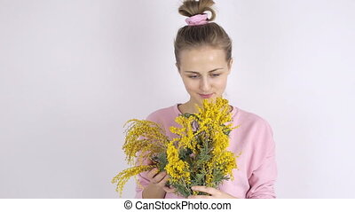 Young woman with fresh mimosa flowers