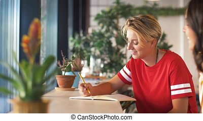 young woman with friend drawing at cafe - people and...