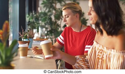 people and friendship concept - young woman with friend drinking coffee drawing to notebook at cafe