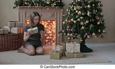 Young woman with gifts in front of Christmas tree