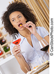 young woman with glass of wine and eating