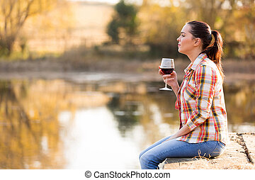 young woman with glass of wine on pier