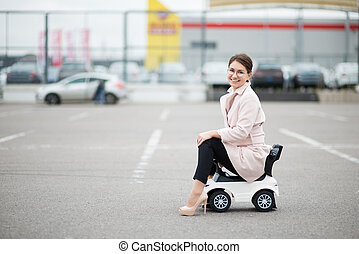 young woman with glasses in a supermarket parking lot sitting on a children's plastic car and smiling