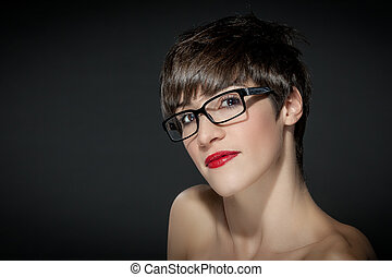 Young woman with glasses in front of a grey background