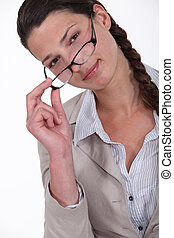 young woman with glasses lowered