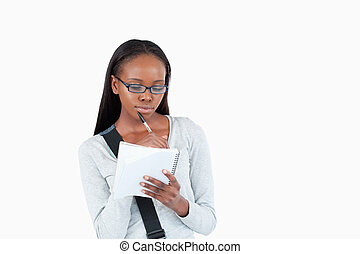 Young woman with glasses reading her notes