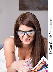 young woman with glasses reading magazine at home