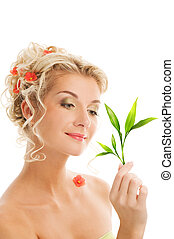 Young woman with green plant. Isolated on whte