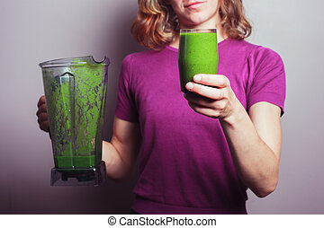 Young woman with green smoothie - A young woman in a purple ...