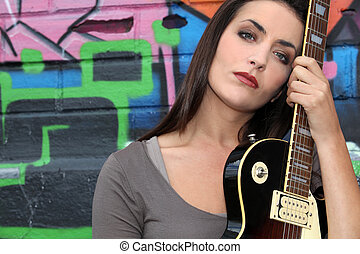 Young woman with guitar in front of a graffiti wall