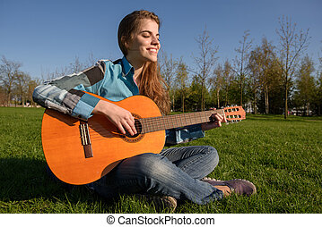 Young woman with guitar outdoor on grass in park