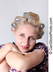 young woman with hair curlers on her head.