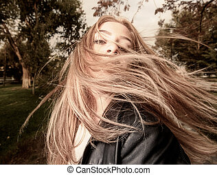 Young woman with hair swept by wind