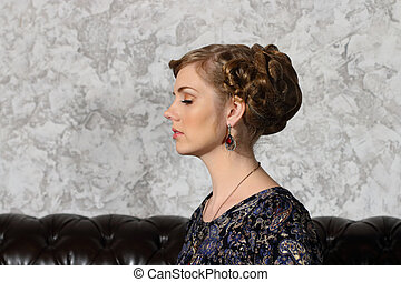 Young woman with hairdo and closed eyes poses on sofa in studio