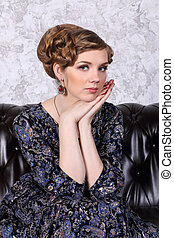 Young woman with hairdo poses with closing eyes on sofa in studio
