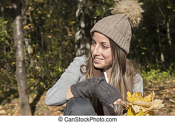 Young woman with hat playing with autumn maple leaves