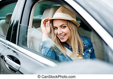 Young woman with hat sitting in car, looking out.