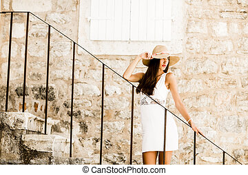 Young woman with hat standing on the stairs outdoor
