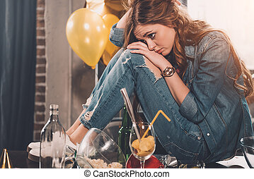 young woman with headache in messy room after party
