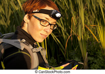 Young woman with headlamp on head and digital compas looking for geocache