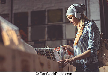 Young woman with headphones browsing vinyl records