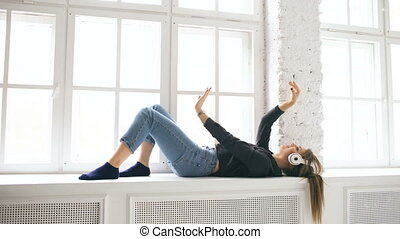 Young woman with headphones listening music and dancing lie on window indoors