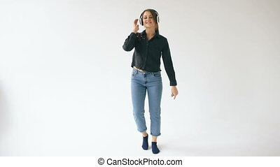 Young woman with headphones listening music and dancing on white background indoors