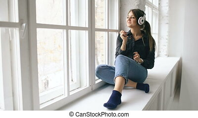 Young woman with headphones listening music and dancing sit on window indoors