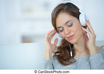 young woman with headphones listening to music from smartphone