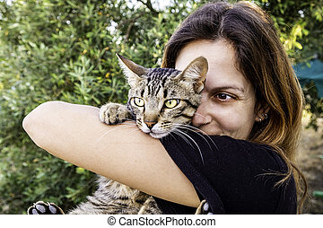 Young woman with her cat near the face