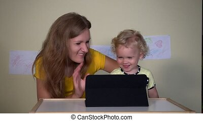 Young woman with her child girl looking funny cartoons on...