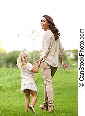 Young woman with her daughter walking in park