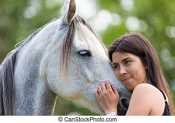 Happy young woman with her horse and strolling