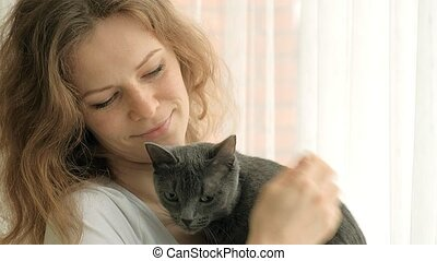 young woman with her lovely grey cat, white background