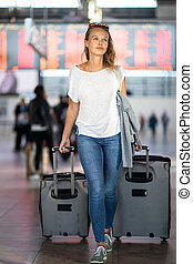 Young woman with her luggage at an international airport