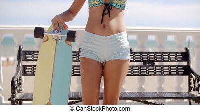 Young woman with her skateboard at the beach